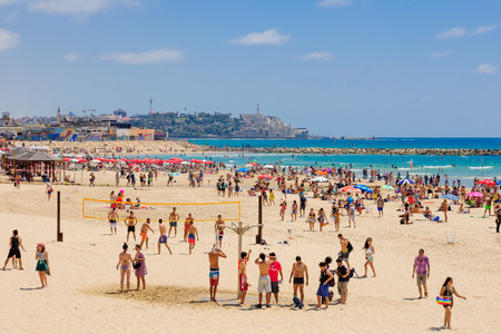 TEL AVIV ISRAEL  JUNE 12 2015: View of the beach of TelAviv and the old city of Jaffa with locals and tourists in TelAviv Israel. Redakční