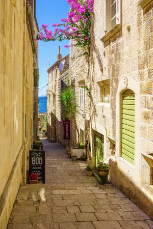 KORCULA, CROATIA - JUNE 25, 2015: An alley in the old city of Korcula, with local businesses, in Dalmatia, Croatia Editorial