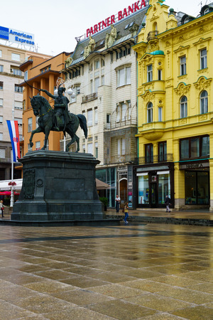 local business: ZAGREB, CROATIA - JUNE 24, 2015: Scene of Ban Jelacic Square, with the statue of Ban Jelacic, local business, locals and tourists, in Zagreb, Croatia