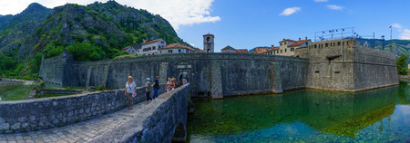 dated: KOTOR, MONTENEGRO - JUNE 29, 2015: Panoramic view of The North Gate River Gate, dated 1540, and the old town walls, with locals and tourists, in Kotor, Montenegro