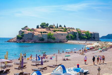 sveti: SVETI STEFAN, MONTENEGRO - JUNE 29, 2015: Beach scene, with the old village, locals and tourists, in Sveti Stefan, Montenegro
