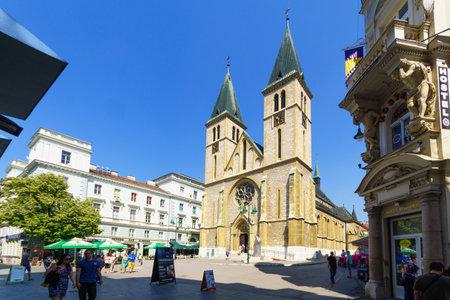 and sacred: SARAJEVO, BIH - JULY 05, 2015: Scene of the Sacred Heart Cathedral, with locals and tourists, in Sarajevo, Bosnia and Herzegovina