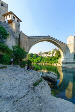 most: MOSTAR, BIH - JULY 05, 2015: The restored Old Bridge Stari Most, with locals and tourists, in Mostar, Bosnia and Herzegovina