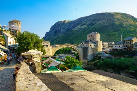 most: MOSTAR, BIH - JULY 05, 2015: Scene of the old city and the restored Old Bridge Stari Most, with locals and tourists, in Mostar, Bosnia and Herzegovina