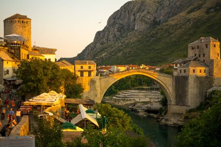 most: MOSTAR, BIH - JULY 05, 2015: Sunset scene of the old city and the restored Old Bridge Stari Most, with locals and tourists, in Mostar, Bosnia and Herzegovina