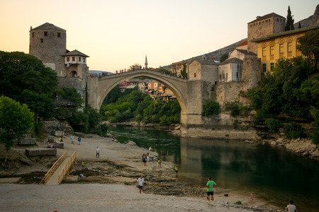 neretva: MOSTAR, BIH - JULY 05, 2015: The restored Old Bridge Stari Most on sunset, with locals and tourists, in Mostar, Bosnia and Herzegovina Editorial