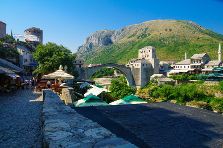 neretva: MOSTAR, BIH - JULY 06, 2015: Scene of the old city and the restored Old Bridge Stari Most, with locals and tourists, in Mostar, Bosnia and Herzegovina