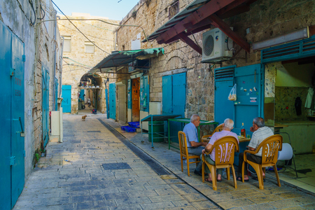 acre: ACRE, ISRAEL - OCTOBER 01, 2015: Alley scene in the old city, with locals at a cafe, in Acre, Israel