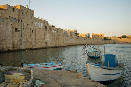 acre: Fishing nets and boats, and the old sea wall in the old city of Acre, Israel