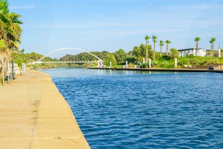 joggers: HADERA, ISRAEL - SEPTEMBER 27, 2015: View of Hadera River Nahal Hadera Park, the Harp Nevel Bridge, visitors and joggers. Northern Israel Editorial