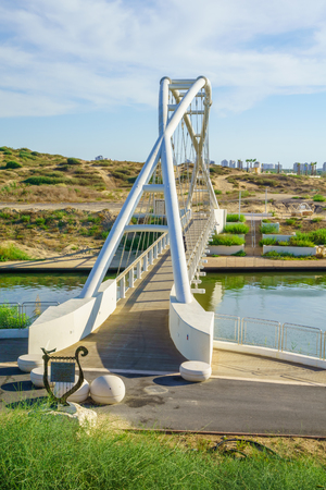 nahal: The Harp Nevel Bridge in Hadera River Nahal Hadera Park, Northern Israel. The sign describes the bridge and includes safety rules.