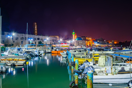 acre: ACRE, ISRAEL - OCTOBER 18, 2015: Local fishing boats, yachts with and nearby monuments, at night in the fishing harbor in the old city of Acre, Israel. Acre was a major harbor city for many centuries Editorial