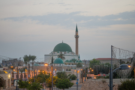 continuously: ACRE, ISRAEL - OCTOBER 18, 2015: A business street and the Ahmed el-Jazzar Mosque, in the old city of Acre, Israel. Acre is one of the oldest continuously inhabited sites in the world.