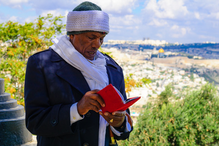 JERUSALEM, ISRAEL - NOVEMBER 11, 2015: An Ethiopian Jewish man pray at the Sigd, with the old city in the background, in Jerusalem, Israel. The Sigd is an annual holiday of the Ethiopian Jewry