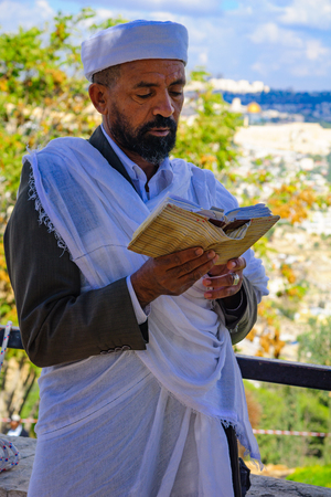 jewry: JERUSALEM, ISRAEL - NOVEMBER 11, 2015: An Ethiopian Jewish man pray at the Sigd, with the old city in the background, in Jerusalem, Israel. The Sigd is an annual holiday of the Ethiopian Jewry