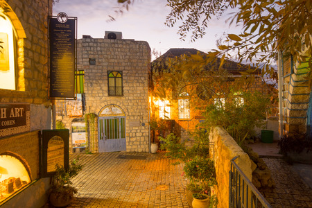 israel: SAFED, ISRAEL - NOVEMBER 17, 2015: Sunset scene in an ally in the Jewish quarter, with local businesses, in Safed Tzfat, Israel