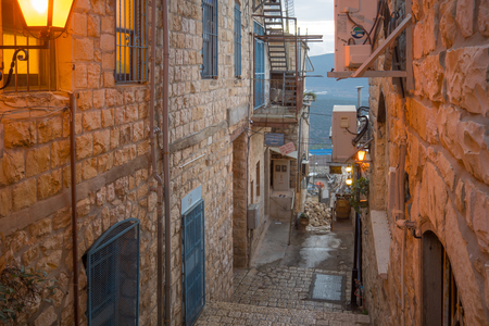 an ally: SAFED, ISRAEL - NOVEMBER 17, 2015: Sunset scene in an ally in the Jewish quarter, with local businesses, in Safed Tzfat, Israel