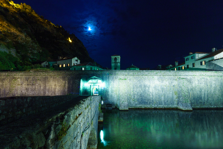 north gate: The North Gate River Gate, dated 1540, and the old town walls, at night, in Kotor, Montenegro