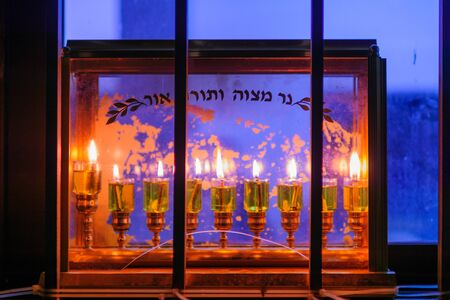 Traditional Menorah (Hanukkah Lamp) with olive oil candles. Text is: Candle of Mitzvah (commandment), Torah (Pentateuch) and Light