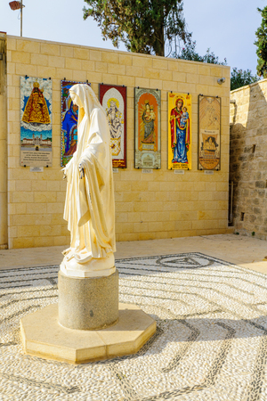 annunciation of mary: NAZARETH, ISRAEL - DECEMBER 16, 2015: A statue of Mary, with donations from various nation in the background, in the Church of the Annunciation, Nazareth, Israel Editorial