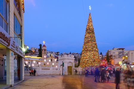 annunciation of mary: NAZARETH, ISRAEL - DECEMBER 16, 2015: Christmas scene of Mary Well square, with the Greek Orthodox Church of the Annunciation, a Christmas tree, locals and tourists, in Nazareth, Israel Editorial