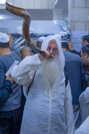 NETIVOT, ISRAEL - JANUARY 13, 2016: Jewish men blows a shofar at the Rabbi Israel Abuhaseira Baba Sali tomb, as part of the annual hillula of his memory. In Netivot, Israel