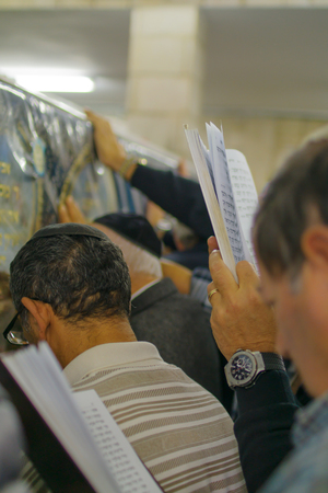 sephardic: NETIVOT, ISRAEL - JAN 13, 2016: Jewish men pray at the Rabbi Israel Abuhaseira Baba Sali tomb, while reaching the mark with their hands, as part of the annual hillula of his memory. Netivot, Israel