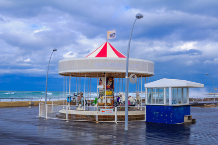 carrousel: TEL-AVIV - JANUARY 25, 2016: Winter scene with a restored carrousel and a commercial area in Tel-Aviv Port, Tel-Aviv, Israel. The port compound was restored as a dining and commercial area