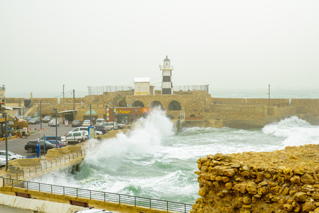 acre: ACRE, ISRAEL - JANUARY 18, 2016: Stormy winter day scene of a Templar Fortress remains, lighthouse, restaurants, visitors and Haifa bay, in the old city of Acre, Israel