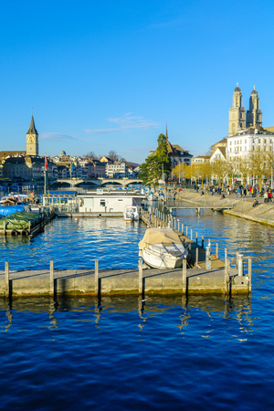 grossmunster cathedral: ZURICH, SWITZERLAND - DECEMBER 24, 2015: View of the Old Town Altstadt and the Limmat River, with the towers of Grossmunster and St. Peter Churches, locals and visitors. In Zurich, Switzerland Editorial
