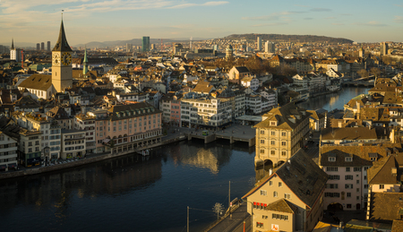 grossmunster cathedral: ZURICH, SWITZERLAND - DECEMBER 24, 2015: Sunset view of the Old Town Altstadt and the Limmat River, with the St. Peter Church, locals and visitors. In Zurich, Switzerland
