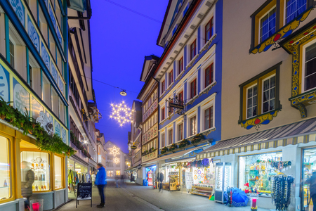 appenzeller: APPENZELL, SWITZERLAND - DECEMBER 30, 2015: Evening scene with painted houses, Christmas decorations, locals and visitors, in Appenzell, Switzerland