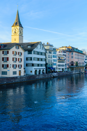 altstadt: ZURICH, SWITZERLAND - DECEMBER 25, 2015: View of the Old Town Altstadt and the Limmat River, with the clock tower of St. Peter Churches, locals and visitors. In Zurich, Switzerland