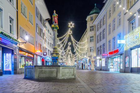 justitia: WINTERTHUR, SWITZERLAND - DECEMBER 26, 2015: Night scene of Marktgasse Street, with the Justitia Fountain, Christmas decorations, locals and visitors in Winterthur, Switzerland Editorial