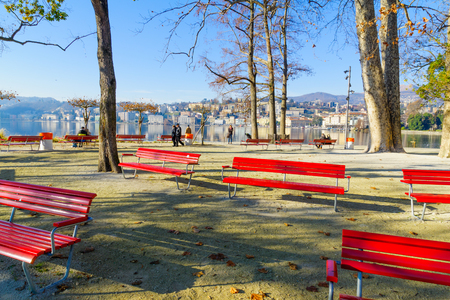 lakefront: LUGANO, SWITZERLAND - DECEMBER 29, 2015: View of the Parco Civico garden and the lakefront, with locals and visitors, in Lugano, Ticino, Switzerland