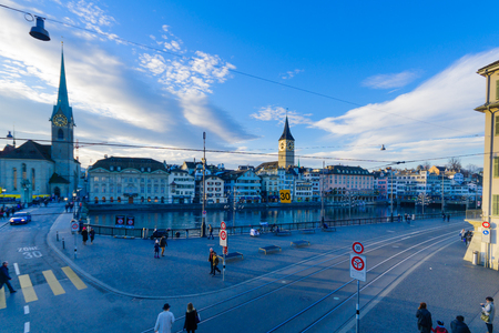 altstadt: ZURICH, SWITZERLAND - DECEMBER 24, 2015: Sunset view of the Old Town Altstadt and the Limmat River, with the Fraumunster and St. Peter Churches, locals and visitors. In Zurich, Switzerland Editorial