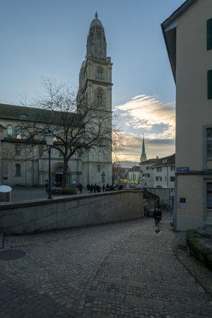 grossmunster cathedral: ZURICH, SWITZERLAND - DECEMBER 24, 2015: Sunset view of the Grossmunster great minster Church, with locals and visitors. In Zurich, Switzerland