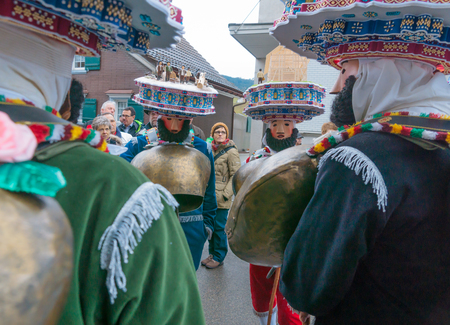 URNASCH, SWITZERLAND - DECEMBER 31, 2015: New Year Mummers, and spectators in Urnasch, Appenzell, Switzerland. Its part of the Silvesterchlausen tradition of greeting for the New Year