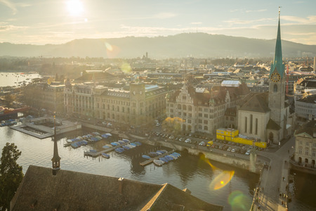Sunset view of the west bank of the Limmat River, with the Fraumunster Women Minster Church, Lake Zurich, and a sun flare. In Zurich, Switzerland