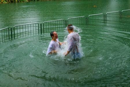 baptismal: YARDENIT, ISRAEL - JANUARY 19, 2016: Pilgrims baptizing in the Jordan River, in the Yardenit Baptismal Site. Northern Israel Editorial