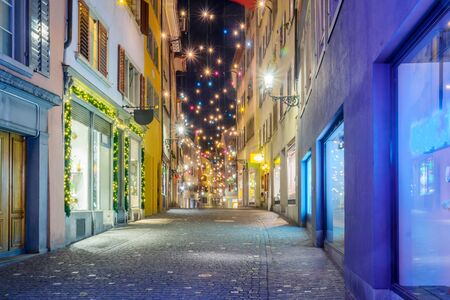 Night street scene in the Old Town Altstadt, with Christmas decoration lamps in multiple colors, in Zurich, Switzerland