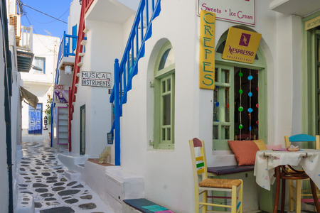 MYKONOS, GREECE - OCTOBER 02, 2011: A street with typical Greek houses and local businesses, in Mykonos, Mykonos Island, Greece 新聞圖片