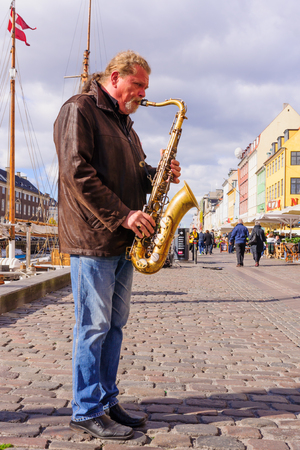 17th: COPENHAGEN, DENMARK - OCTOBER 01, 2010: A musician and cafes scene on Nyhavn, with locals and visitors, in Copenhagen, Denmark. Nyhavn is a 17th century harbor in Copenhagen Editorial