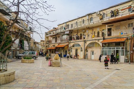 hasidim: JERUSALEM, ISRAEL - FEBRUARY 25, 2016: Street scene of the Jewish Holyday Purim, with locals, some wearing costumes, in Batei Ungarin, the ultra-orthodox neighborhood Mea Shearim, Jerusalem, Israel