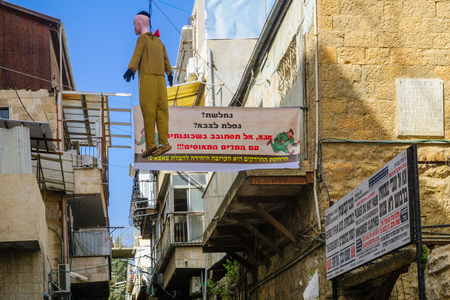 haredi: JERUSALEM, ISRAEL - FEBRUARY 25, 2016: A hanged soldier puppet and posters, part of an ultra-orthodox Jews protest against draft to the military, in the neighborhood of Mea Shearim, Jerusalem, Israel Editorial