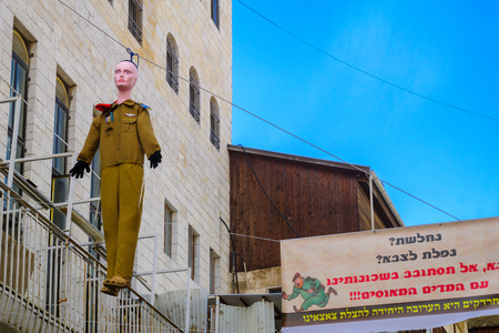 JERUSALEM, ISRAEL - FEBRUARY 25, 2016: A hanged soldier puppet and posters, part of an ultra-orthodox Jews protest against draft to the military, in the neighborhood of Mea Shearim, Jerusalem, Israel Editorial