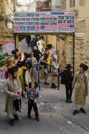 holyday: JERUSALEM, ISRAEL - FEBRUARY 25, 2016: Street scene of the Jewish Holyday Purim, with locals, some wearing costumes, in the ultra-orthodox neighborhood Mea Shearim, Jerusalem, Israel