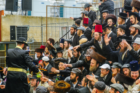 holyday: JERUSALEM, ISRAEL - FEBRUARY 25, 2016: A man pour free wine to the crowd, as part of a celebration of the Jewish Holyday Purim, in the ultra-orthodox neighborhood Mea Shearim, Jerusalem, Israel Editorial
