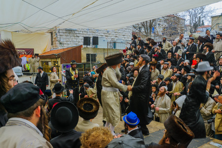 JERUSALEM, ISRAEL - FEBRUARY 25, 2016: Jewish men attend and dance, as part of a celebration of the Jewish Holyday Purim, in the ultra-orthodox neighborhood Mea Shearim, Jerusalem, Israel