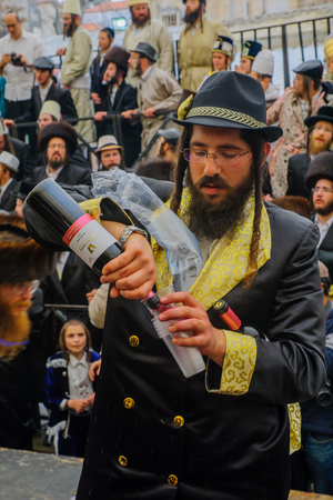 hasidim: JERUSALEM, ISRAEL - FEBRUARY 25, 2016: A man pour free wine to the crowd, as part of a celebration of the Jewish Holyday Purim, in the ultra-orthodox neighborhood Mea Shearim, Jerusalem, Israel Editorial